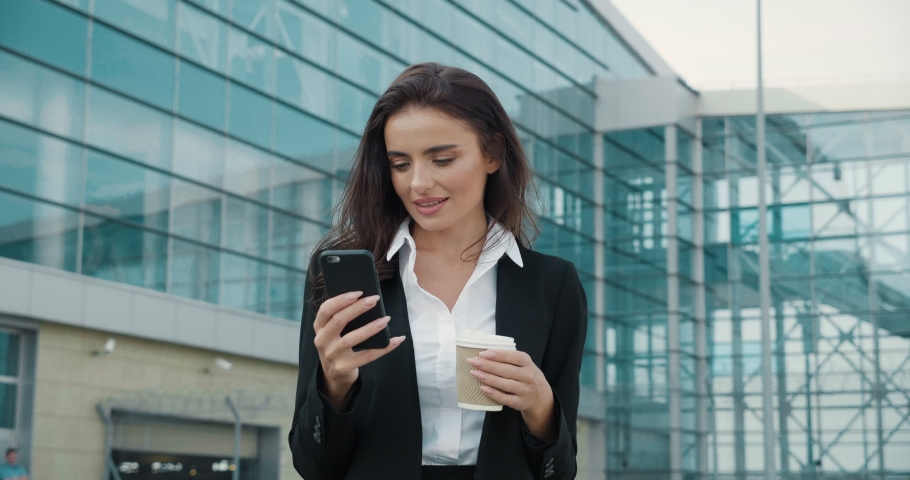 Young Pretty Woman Using Social Networks, Typing Messages Outdoor. Holding Mobile Phone in her Hand. Looking stylish and Attractive. Having well groomed Hair. Charming smile.   Shutterstock HD Video #1041585904