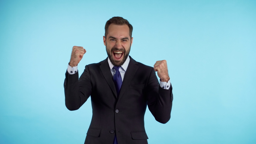 Yes winner gesture. Amazed european businessman with beard shocked, saying yeah. Handsome guy with stylish hairdo surprised to camera over blue background.