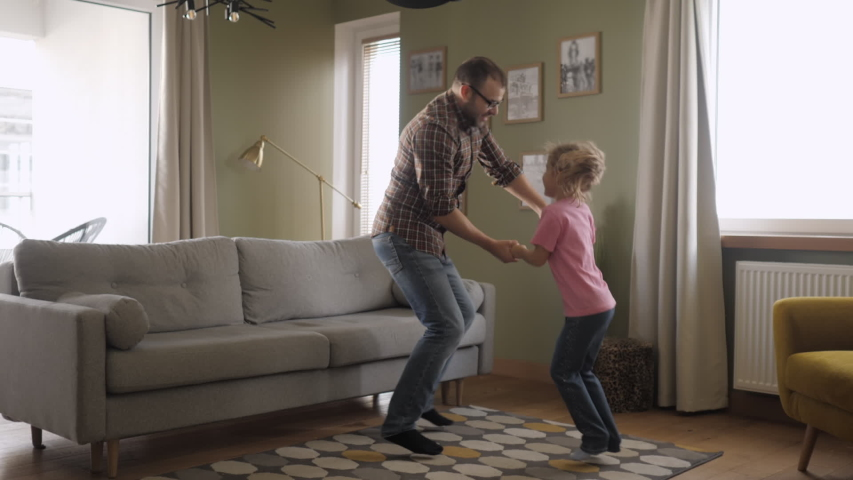 Young Father and Her Daughter Playing in Living Room. Funny Happy Family Father and Daughter are Dancing hold hands and jump at Home. Love Lifestyle Home. Slow Motion. #1041823744