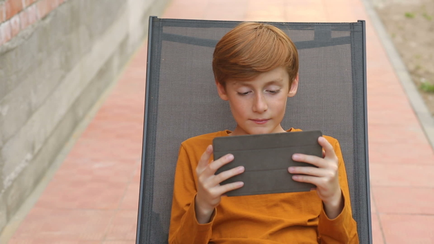 Boy playing a game on a tablet sitting on a sun lounger | Shutterstock HD Video #1041880474