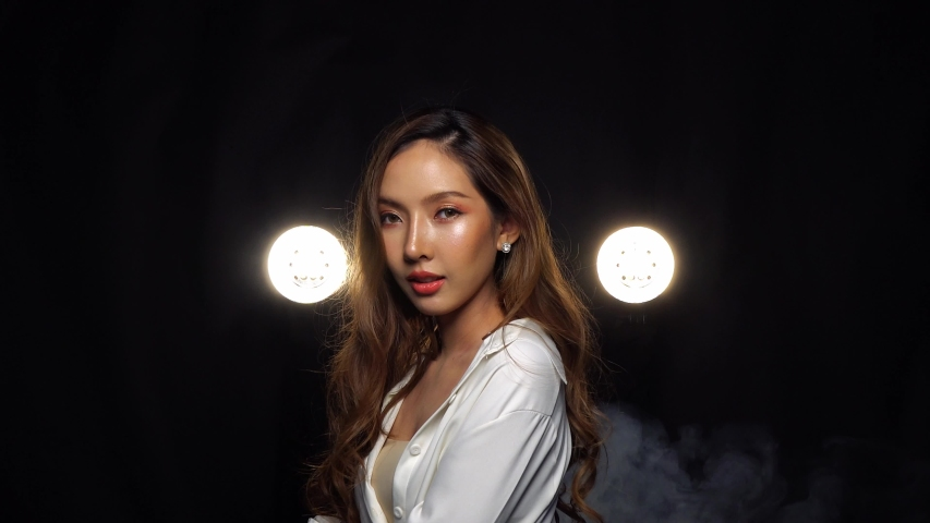A sultry Asian model shows her new face after rhinoplasty in a fashion photo shoot, studio backlit smoke fog dark background, medium shot 4k | Shutterstock HD Video #1042015024
