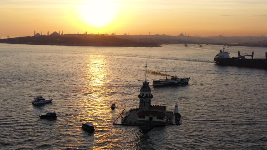 Istanbul Maidens Towers Sunset Sky Aerial. Cargo ship sails into Bosphorus Sea off the Maidens Towers shore. Kiz Kulesi drone footage