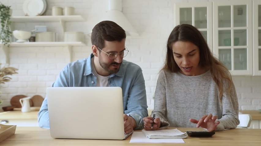 Head shot smiling young mixed race woman discussing family expenses with handsome husband in eyeglasses. Happy married spouses calculating rental payments, utility bills, using computer software. | Shutterstock HD Video #1042155784