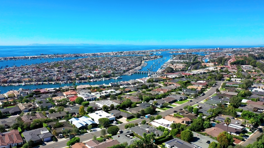Aerial view of Balboa Island luxury coastal neighborhood in Newport Beach, Orange County, California with ocean and harbor below. | Shutterstock HD Video #1042179874
