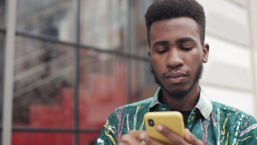 Close up of african student using mobilephone   Shutterstock HD Video #1042267624
