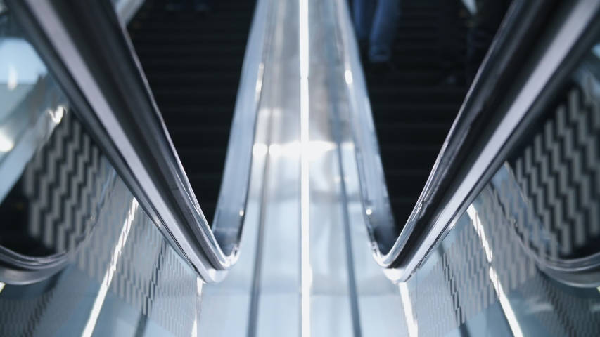Close-up of escalator in airport, train station, subway underground or modern business center. Focus on moving handrail. Unrecognizable people go up and down the stairs | Shutterstock HD Video #1042282924