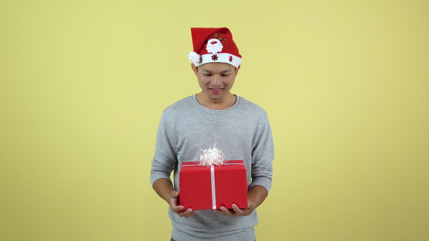 Asian Thai holding a red gift box on yellow background | Shutterstock HD Video #1042399444