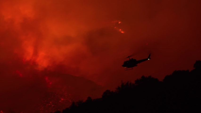 SANTA BARBARA, CALIFORNIA - CIRCA 2010s - a helicopter makes a dramatic water drop at night responding to the Cave Fire near Santa Barbara.