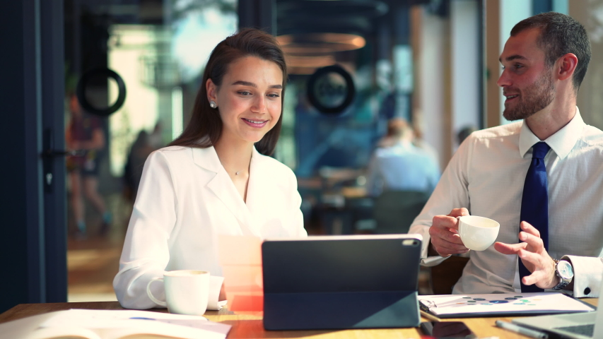 Confident executive managers communicating about business during coffee break at table desktop, successful male and female colleagues talking and smiling during collaboration meeting | Shutterstock HD Video #1042560004