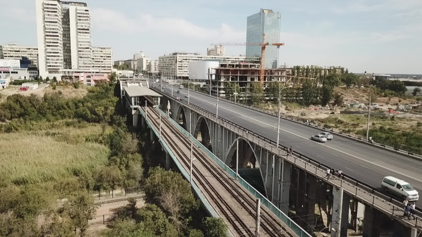Aerial survey of parallel road and railway bridges in the city in sunny weather in the summer near the construction of a multi-storey building a temporary motorway transport junction under the highway | Shutterstock HD Video #1042674724