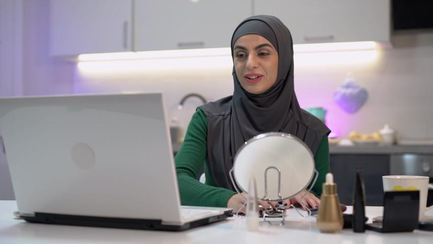 Happy Arabic girl smiling and talking on laptop camera, freelance job, blogging   Shutterstock HD Video #1042696144