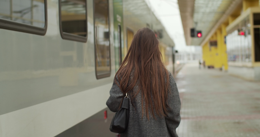 Back view of long-haired girl going on platform ready to get on train slow motion. Unrecognizable woman walking along wagons on railway station travelling. Commuting transportation trip  | Shutterstock HD Video #1042701754