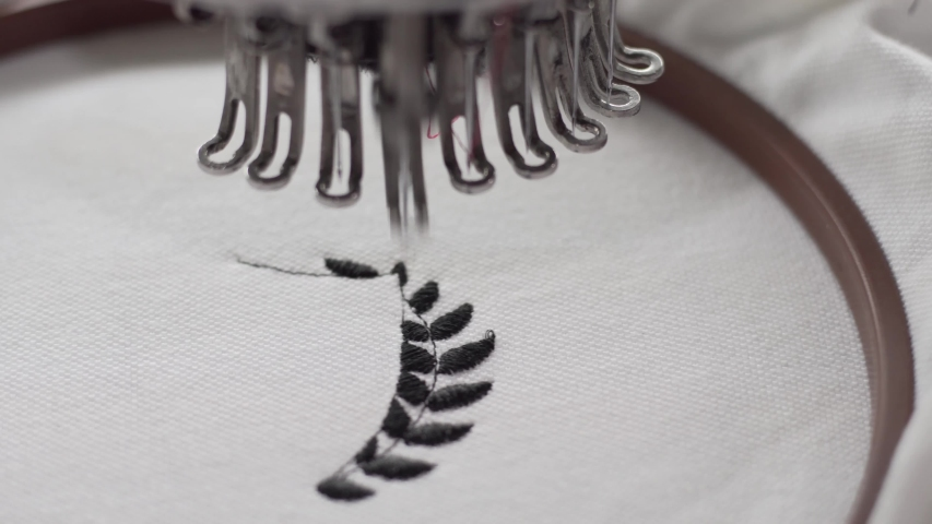 Close up of Sewing needle creating a wider stem on a black Wreath. Machine automaticallyes to next side of wreath once done. White fabric background. | Shutterstock HD Video #1042754644