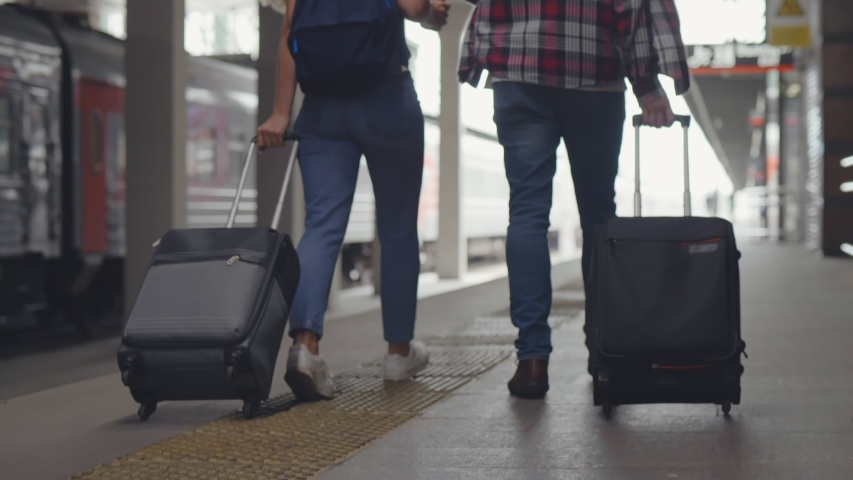 Back view of young cheerful couple imn casual wear walking along railway platform looking for their train, dragging their luggage and talking communicating.   Shutterstock HD Video #1042777774