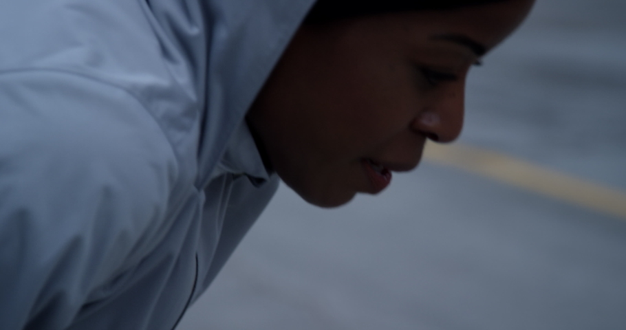 Runner in hooded running jacket leaning over after hard run breathing heavily, out of breath #1042803694