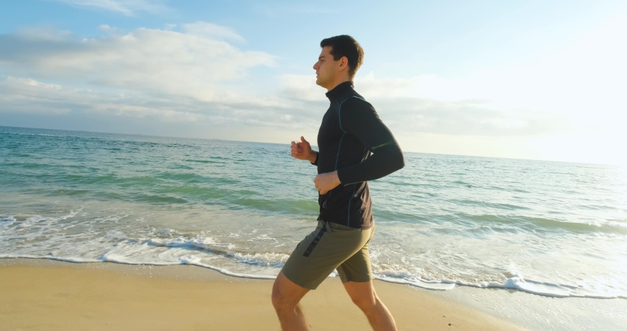 Young fit male runner training outdoors on the morning sunny beach  | Shutterstock HD Video #1042950544