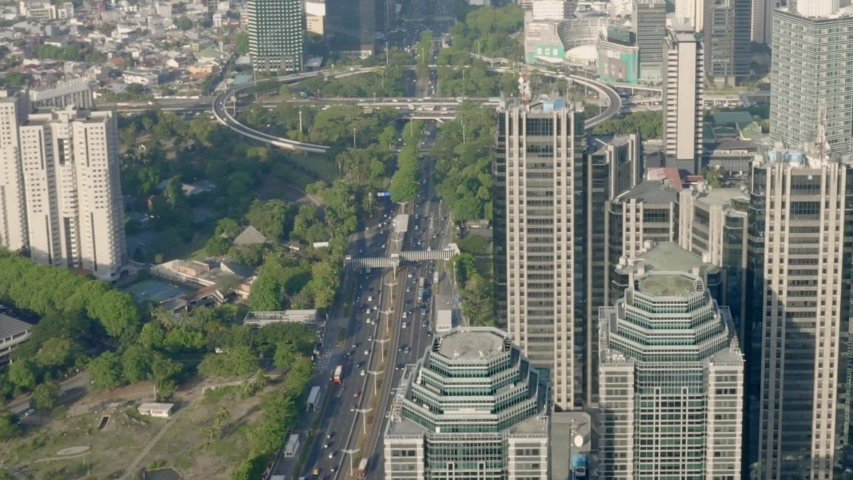 Contemporary iconic cityscape, Jakarta aerial view tilt down above skyscraper office towers & modern city downtown traffic urban scene.   Shutterstock HD Video #1042997134
