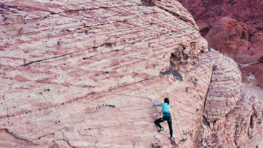 Aerial shot of female rock climber figuring out crux move at Red Rock Canyon | Shutterstock HD Video #1043055934