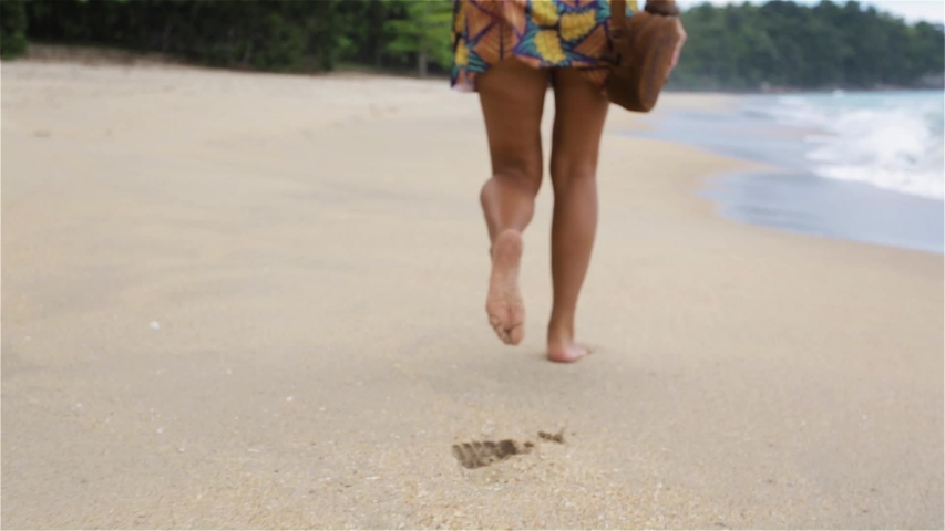 SLOW MOTION:, LOW ANGLE, CLOSE UP,  Unrecognizable woman running in the hot summer sun along the sunny exotic shore in Cook Islands. Carefree girl takes off her flip flops and runs in the sand. | Shutterstock HD Video #1043109604