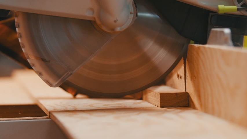 Carpentry - a woodworker cutting the wooden detail with a big circular saw | Shutterstock HD Video #1043183554
