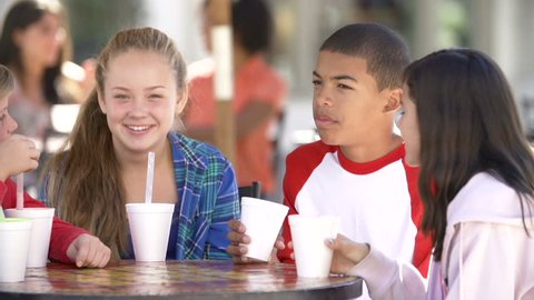 Group of teenage children sitting at tanle in outdoor caf\x8E and talking.Shot on Sony FS700 at frame rate of 25fps