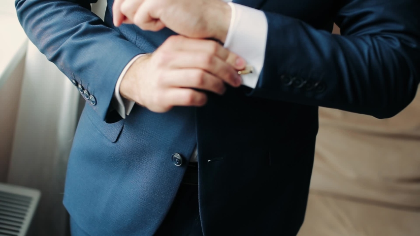 Young man put on jacket. Dressing for celebration event, business meeting or wedding. | Shutterstock HD Video #1043221024