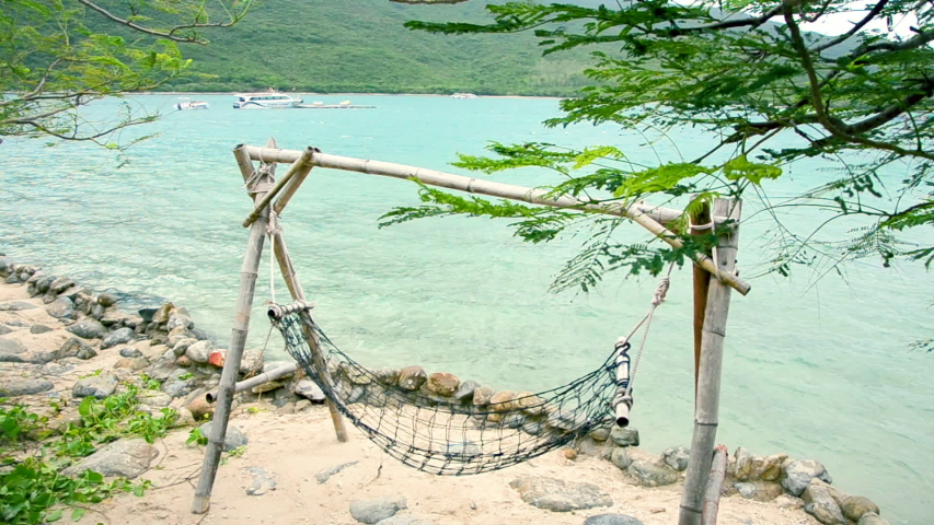 On the ocean coast, a beach hammock swaying in the wind and on small waves. On the horizon of the island, speed boat, jet skis. | Shutterstock HD Video #1043235274