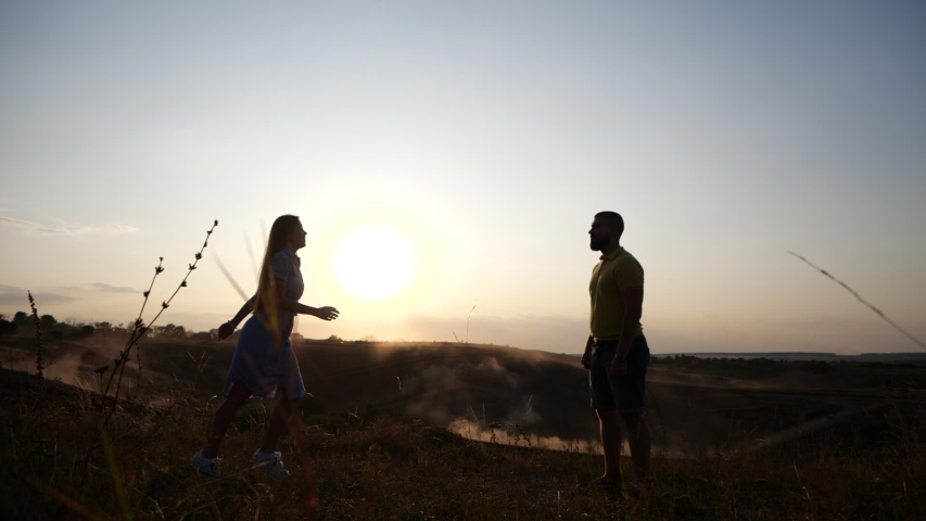 Young girl runs in slow motion toward a bearded young man and kisses him. Couple in rural landscape at breathtaking golden sunset. | Shutterstock HD Video #1043681464