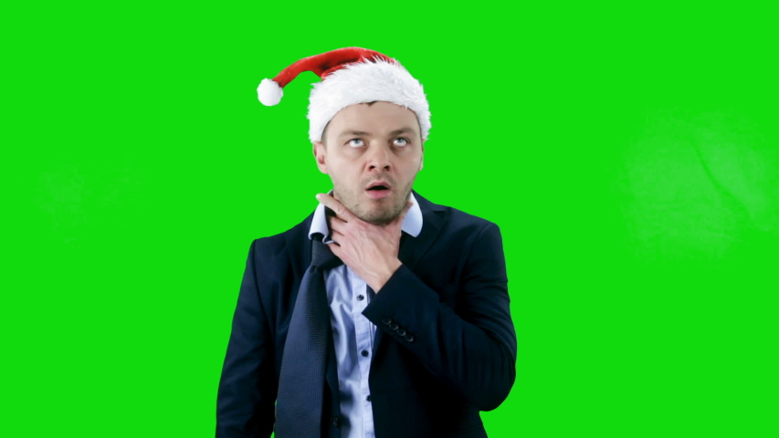 Young business man wearing santa hat tired and very sleepy on green background. Chroma key  | Shutterstock HD Video #1043923624