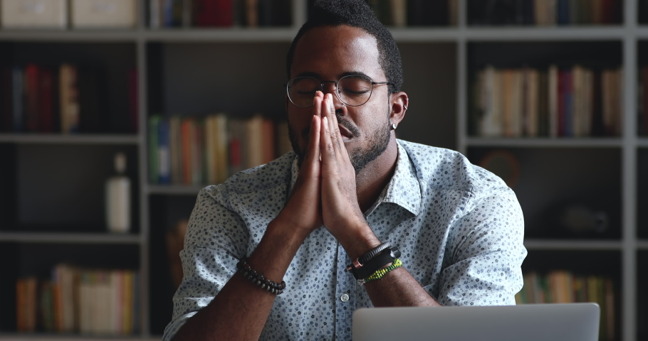 Serious african man asking for help concerned about problem or concentrating mind at work, religious mixed race male student worker sit with eyes closed put hands in prayer praying with hope concept | Shutterstock HD Video #1044100534