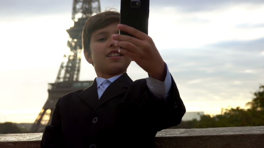 Beautiful teenager boy is making selfie on the phone on the background of the Eiffel tower, Paris, France | Shutterstock HD Video #1044717454
