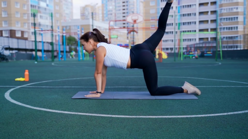 The girl trains the hip and gluteal muscles. Swing your leg from the bar with your leg bent on the press. | Shutterstock HD Video #1044759094