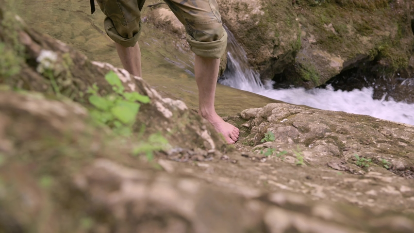 Closeup. Legs of a man. Traveler goes barefoot on rocky road, climbs up by river | Shutterstock HD Video #1044769354