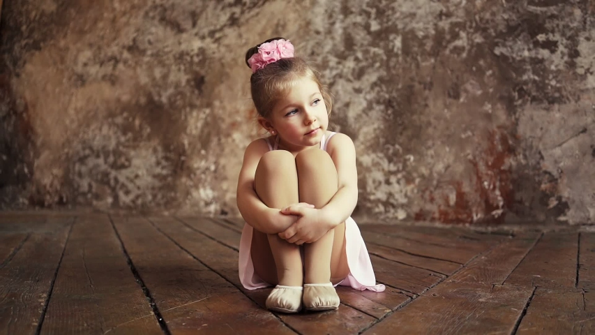 Sad little cute baby girl with bows on her head sitting on the floor cross-legged. Slow motion. Shooting on the Steadicam. | Shutterstock HD Video #1044791344