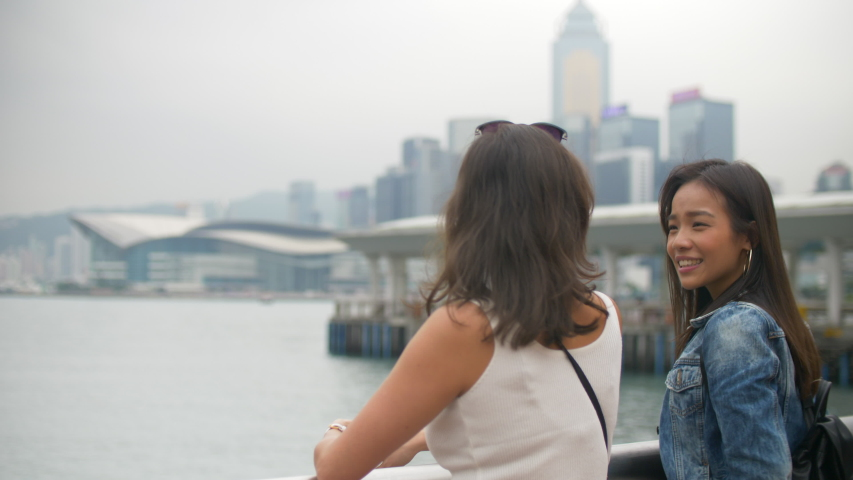 Two Attractive Girls Talk by the Pier with Water and Buildings Around 4k    Shutterstock HD Video #1044832444