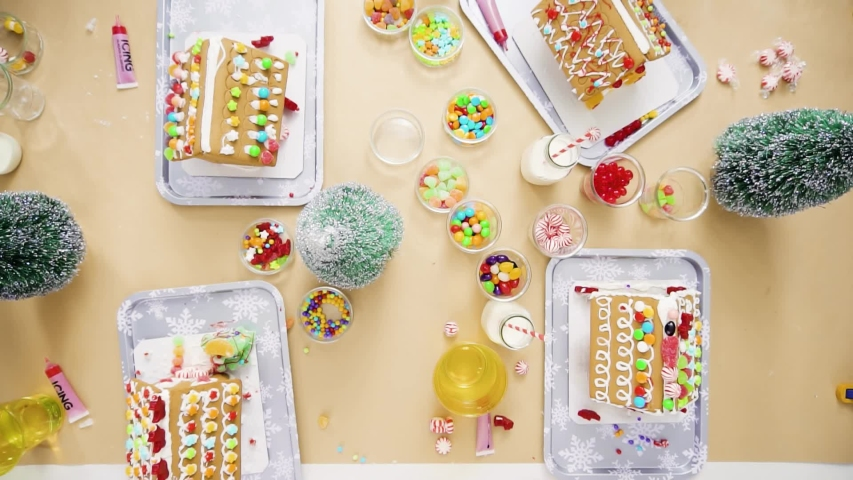 Time lapse. Flat lay. Step by step. Kids decorating small gingerbread houses at the Christmas craft party.   Shutterstock HD Video #1044886174