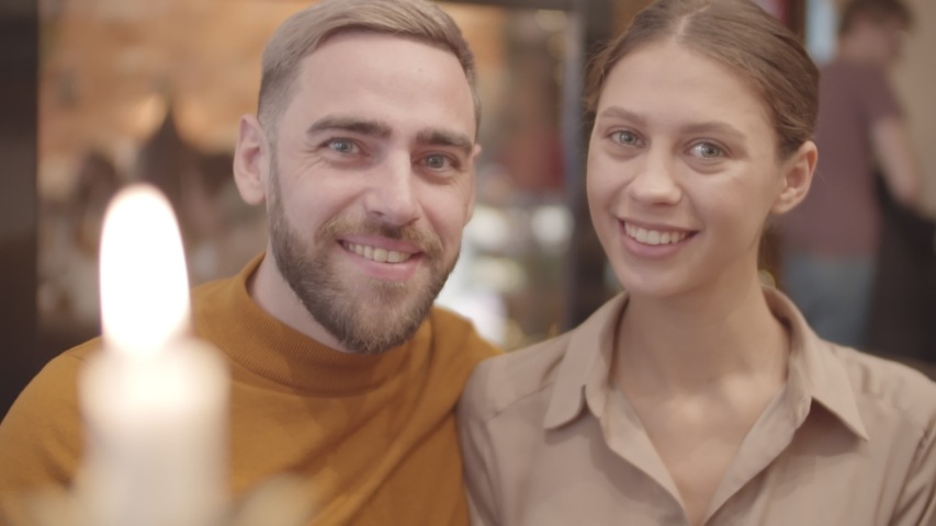 Close up of young handsome man and beautiful woman sitting together, looking at camera and smiling | Shutterstock HD Video #1044962014