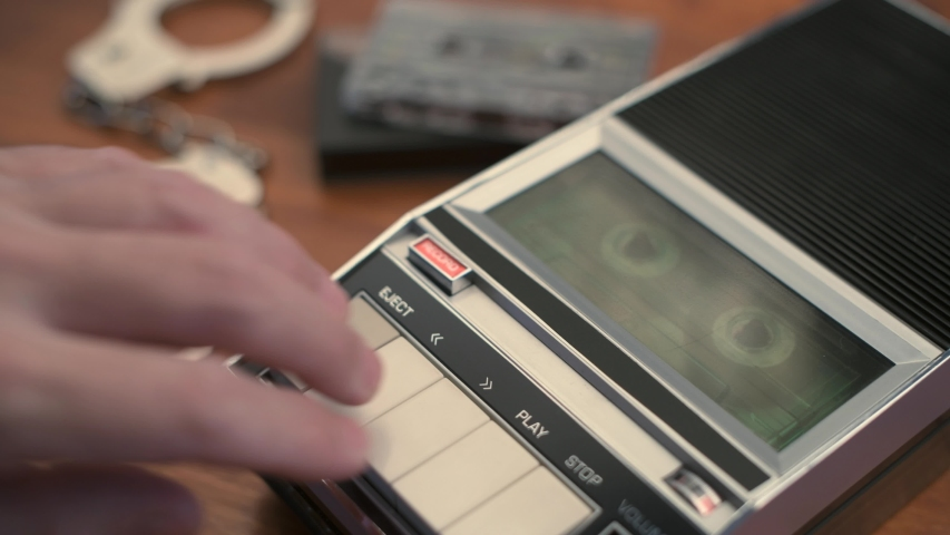 Police detective investigator playing audio cassette tape with recorded interview and interrogation statement   Shutterstock HD Video #1044971914