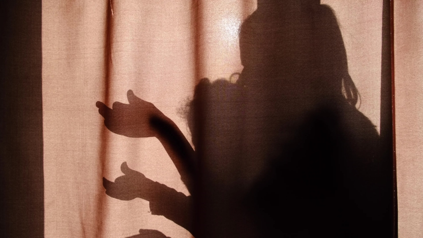 Silhouette of unrecognizable mother and child of primary school age telling stories using shadow presents talking dog's heads when sitting behind the curtains at home and spending time together | Shutterstock HD Video #1044983734