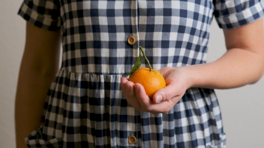 Young Caucasian woman holds fresh mandarin orange and presents ripe sweet tangerine before eating. White girl in country plaid dress spins, moves citrus fruit in hands. Benefits of fruits, vitamins. | Shutterstock HD Video #1045005034