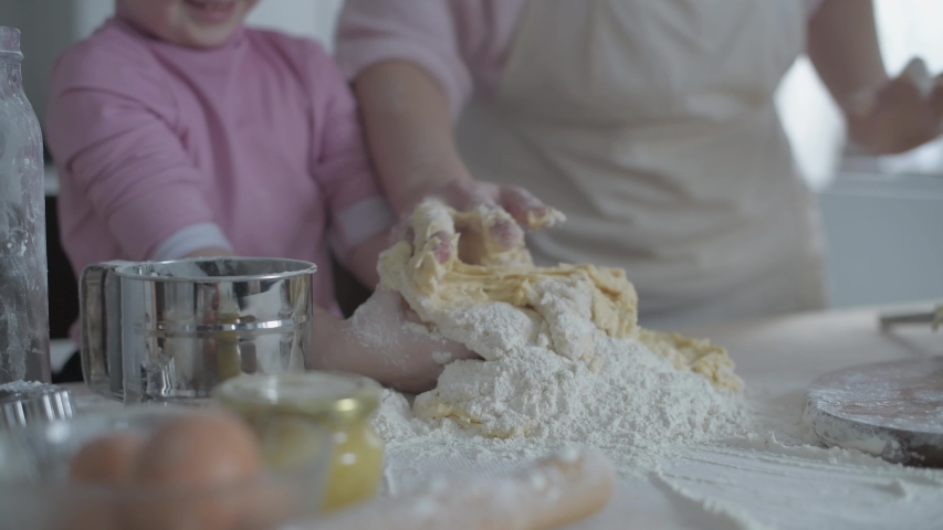 Mom teaches daughter to cook dough. Girl learns to cook pastries. Kneading the dough together. Roll out the dough for baking. Wonderful family in the spacious kitchen prepares food. Holiday cooking | Shutterstock HD Video #1045024294