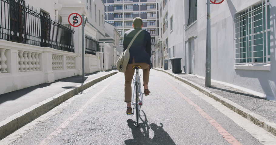 Rear view of a young Caucasian businessman on the go in the city, riding a bike in the street, slow motion | Shutterstock HD Video #1045109644