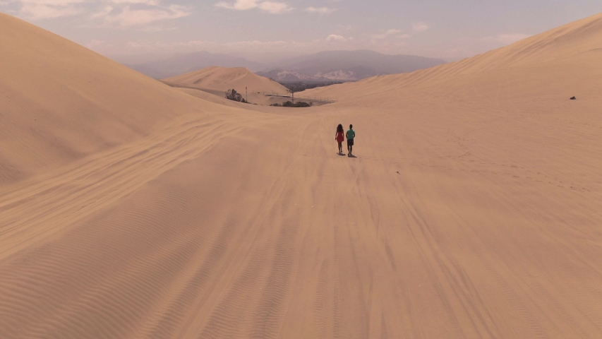 Sandy desert oasis lake. DRONE. Water in middle of hot sand desert. Romantic, holiday, couple, honeymoon, scenic shot, with sand and footprints. Tourism shot in Huacachina, Peru. Epic, dramatic shot. | Shutterstock HD Video #1045192954