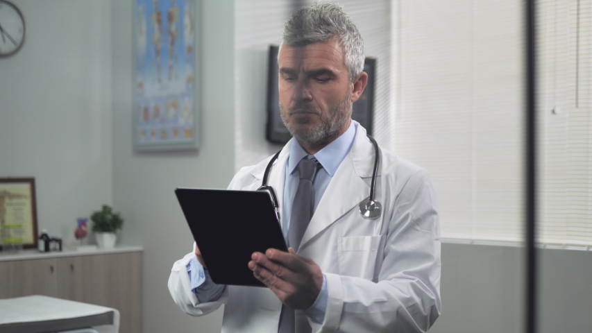 Male doctor behind a glass using tablet in office writes patient diagnosis prescription 4k | Shutterstock HD Video #1045193944