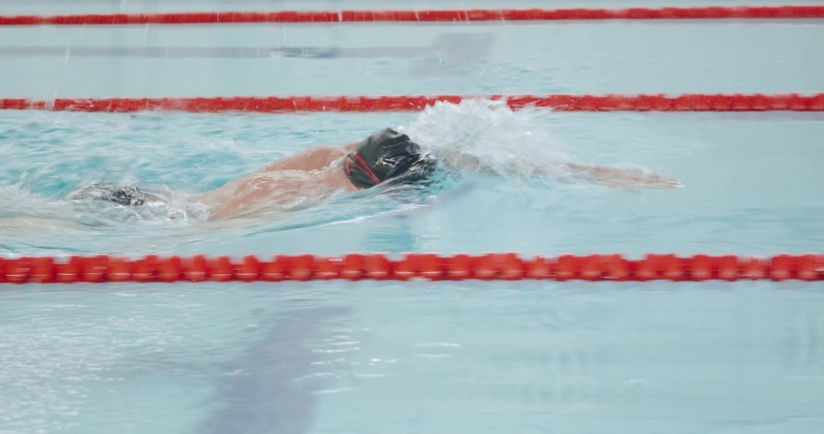 Young athletic man swimmer swims in the pool, man swimming and training in the water. | Shutterstock HD Video #1045215754