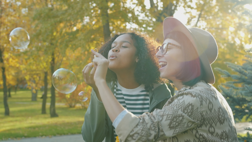 Portrait of happy girls friends blowing soap bubbles in park in autumn laughing having fun enjoying funny activity. Happiness and friendship concept. | Shutterstock HD Video #1045402204