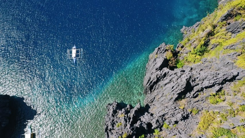 Aerial top down view of boat moving in open sea with clear and turquoise water on sunny day. Boat left the tropical lagoon. El Nido, Palawan island, Philippines | Shutterstock HD Video #1045871764