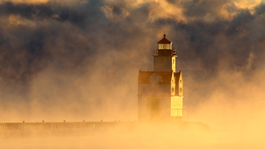 Scenic Lake Michigan lighthouse amid swirling storm of fog at sunrise on a very cold Winter day, seamless loop.