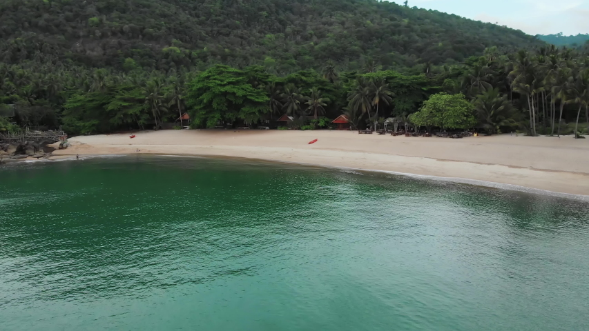 Aerial view of scenery beach. Travel to wild jungles of Thailand. Sea waves leak white sand. Palm trees pass below the drone   Shutterstock HD Video #1046694004