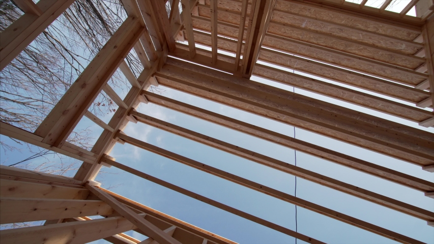 View from below of ceiling beams through which the blue sky is seen, and interior of spacious room in frame house under construction   Shutterstock HD Video #1046725714